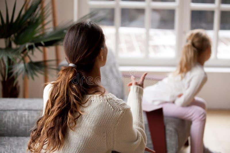 Hintere Ansicht an der Mutter, die Tochter, Kinderrüge und punishme schilt stockfotos