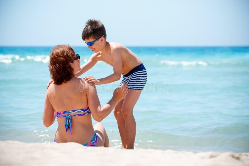 Hintere Ansicht der Mutter und der Sohn, der tropischen Strand genießt, machen Urlaub stockfotos