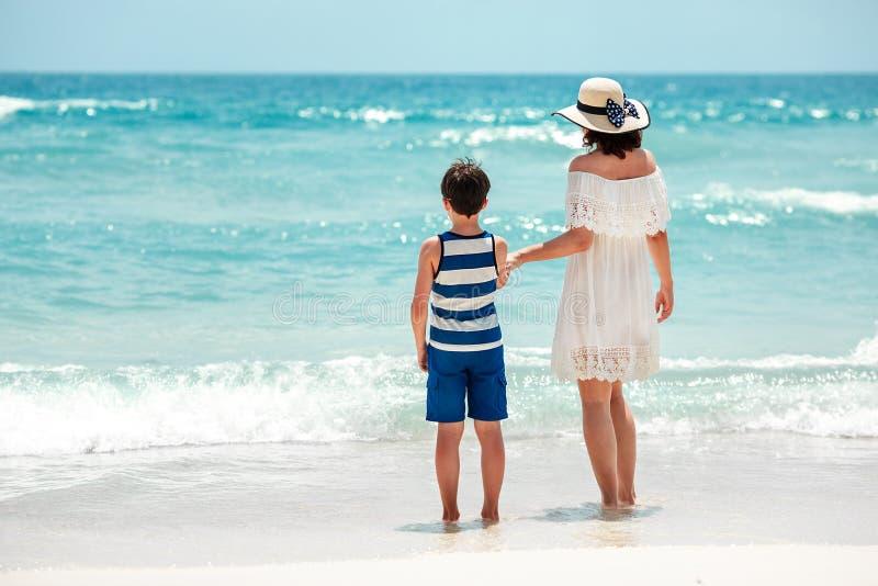 Hintere Ansicht der Mutter und des Sohns am thailändischen Strand lizenzfreies stockfoto