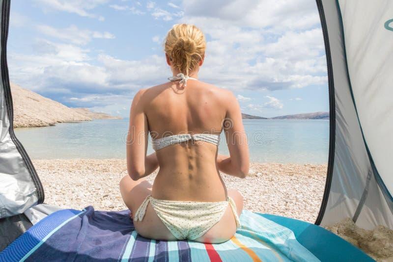 Hintere Ansicht der schönen jungen kaukasischen Frau, die Sommersonne auf dem Mittelmeerstrand geschützt vor Hitze und Sonnenbrän lizenzfreies stockfoto