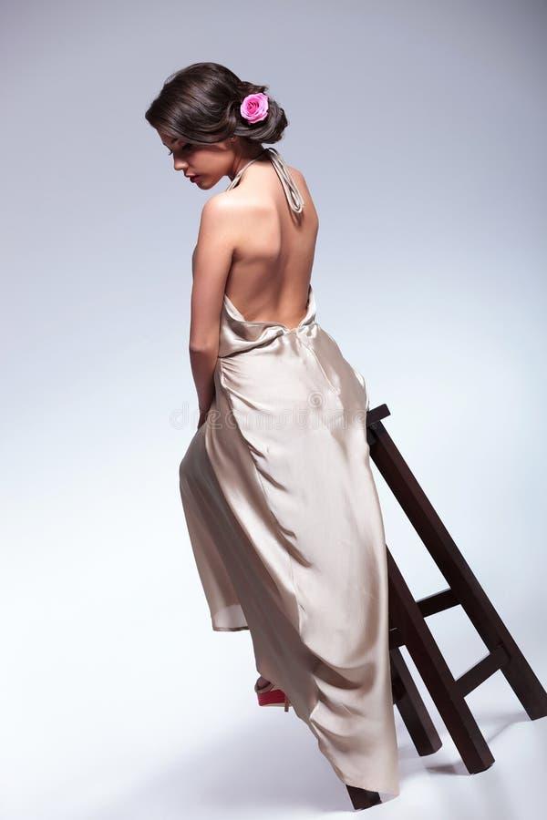 Hintere Ansicht der Schönheitsfrau auf Stuhl lizenzfreie stockbilder