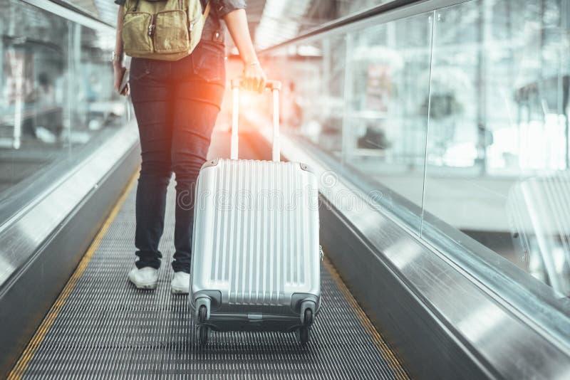 Hintere Ansicht der Schönheitsfrau reisend und Koffer auf esca halten stockfoto