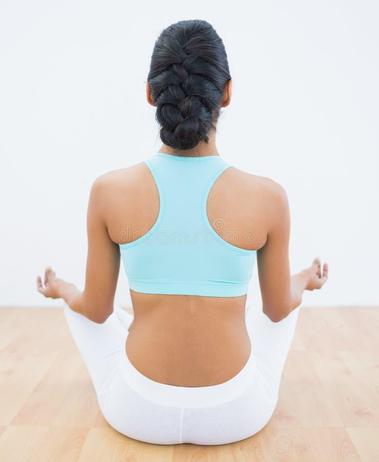 Hintere Ansicht der schlanken ruhigen Frau, die in Lotussitz meditiert stockbilder