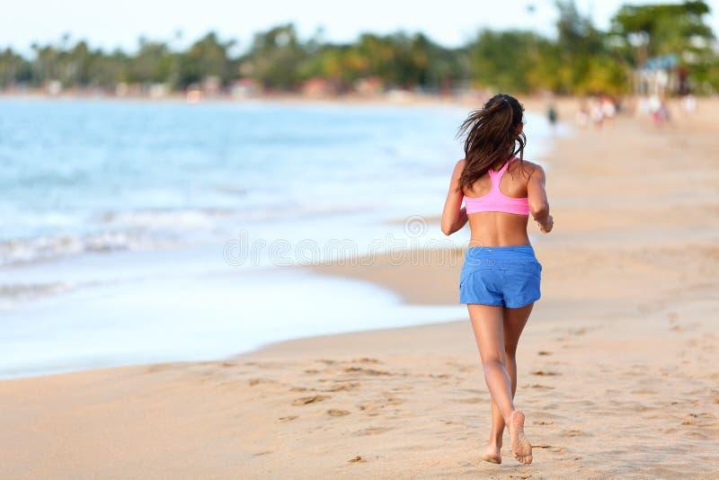 Hintere Ansicht der sportlichen Frau laufend auf Strand lizenzfreies stockfoto
