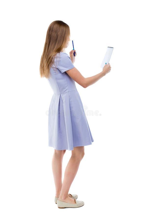 Hintere Ansicht der Standfrau nimmt Kenntnisse in einem Notizbuch lizenzfreies stockbild
