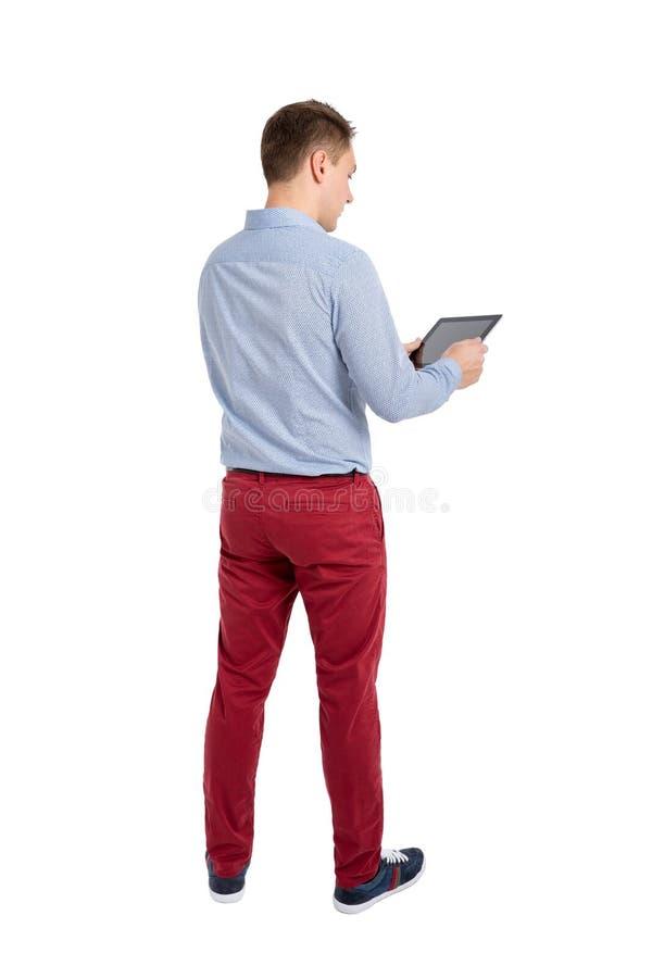 Hintere Ansicht der Stellung von jungen Männern und der Anwendung einer Tablette stockfoto