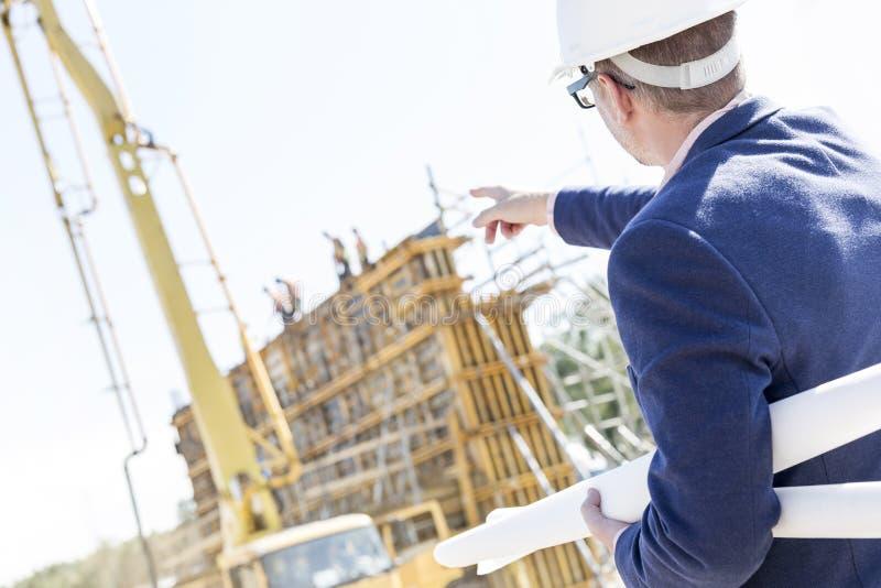 Hintere Ansicht des Architekten Pläne beim Zeigen halten auf Baustelle stockbild