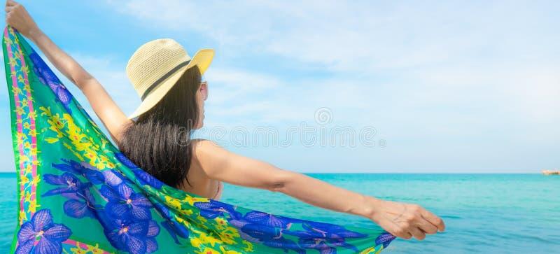 Hintere Ansicht des Asiatinabnutzungsbadeanzugs und der ge?ffneten Arme am tropischen Strand am sonnigen Tag mit sch?nem blauem H lizenzfreie stockfotografie