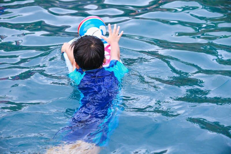 Hintere Ansicht des asiatischen Jungen mit Trittbrett und des Balls im Pool outdoor stockfotografie