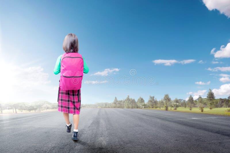 Hintere Ansicht des asiatischen netten Mädchens mit rosa Rucksack gehend auf die Straße, die geht zu schulen lizenzfreie stockfotos