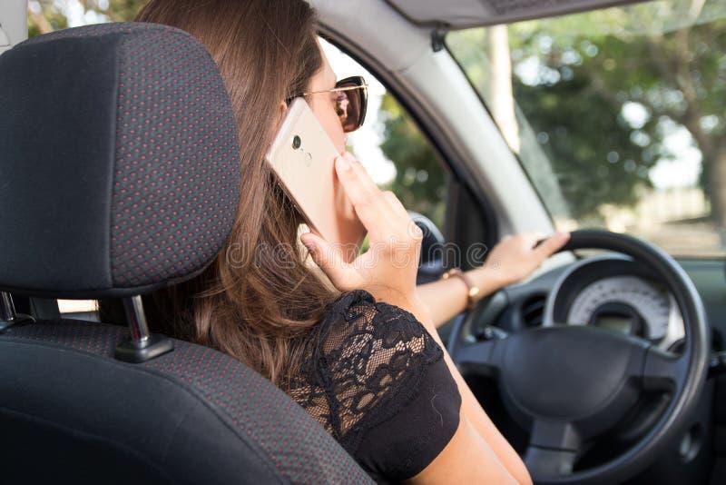 Hintere Ansicht des Autofahrens und der Gespräche der jungen Frau am intelligenten Telefon lizenzfreie stockfotos