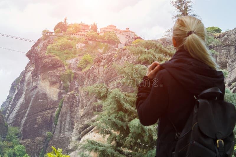 Hintere Ansicht des blonden Mädchens im Schwarzen mit Rucksack in den Bergen bei Sonnenuntergang lizenzfreie stockfotos