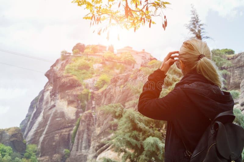 Hintere Ansicht des blonden Mädchens im Schwarzen mit Rucksack in den Bergen bei Sonnenuntergang stockbilder