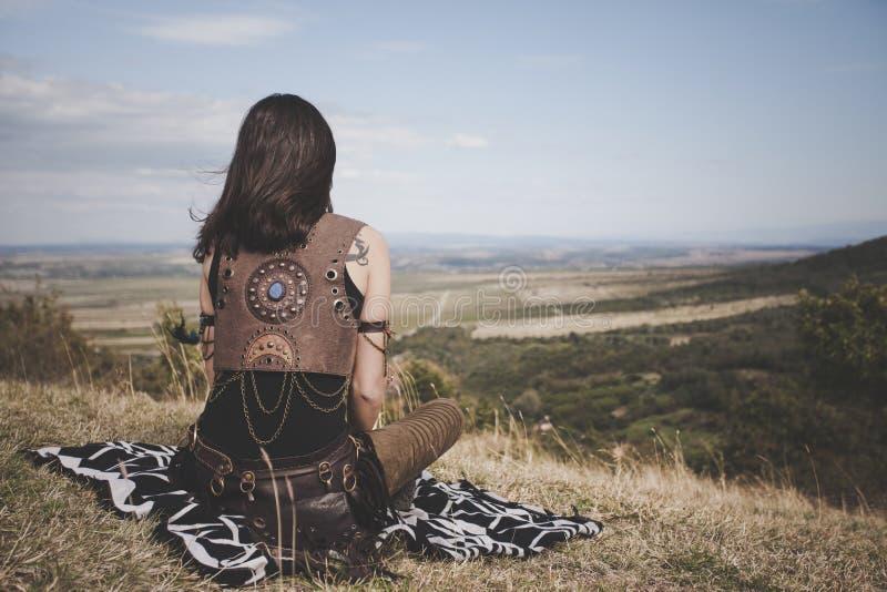 Hintere Ansicht des Boho-Mädchens auf einem Hügel, der weit im Abstand schaut stockbild