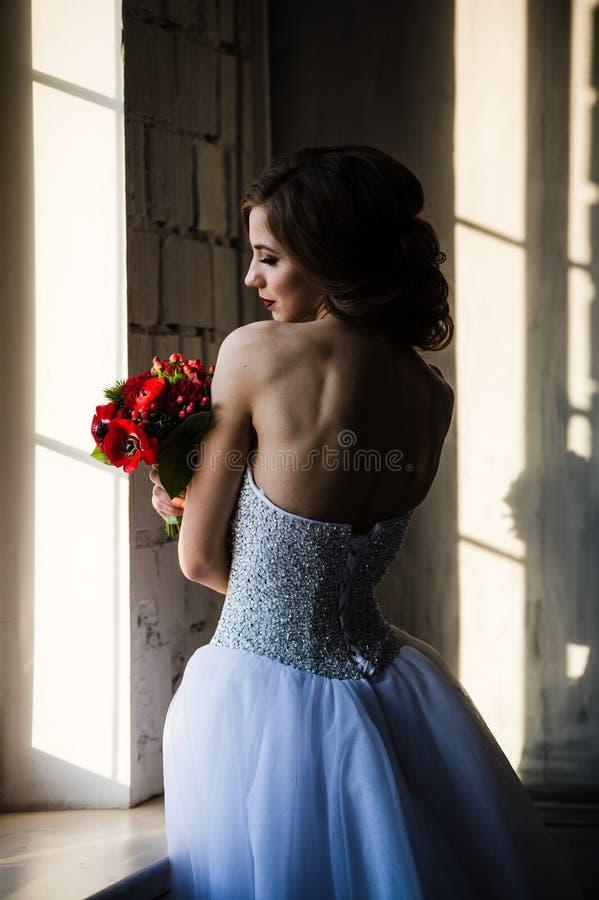 Hintere Ansicht des Brautschattenbildes nahe dem Fenster riecht die roten Blumen stockbilder
