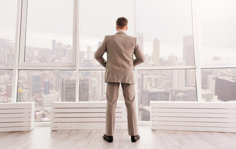 Hintere Ansicht des ernsten Geschäftsmannes stehend im Büro lizenzfreie stockfotografie
