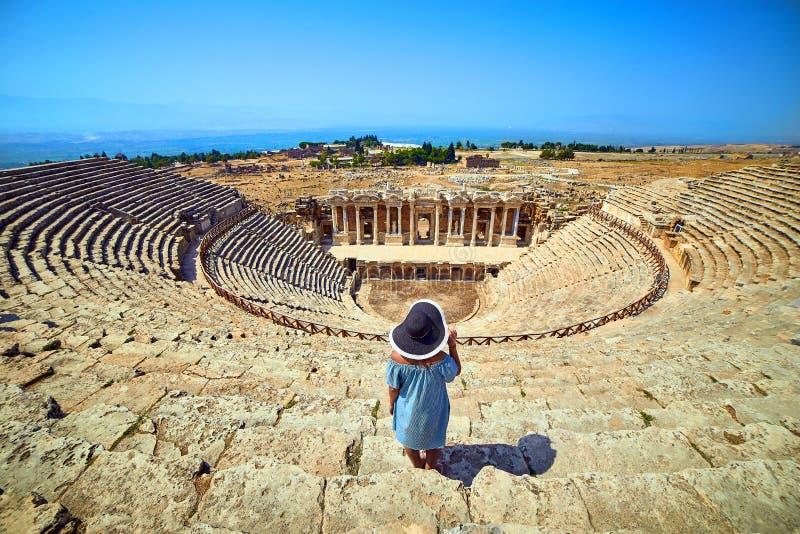 Hintere Ansicht des Frauenreisenden im Hut, der ?berraschende Amphitheaterruinen in altem Hierapolis, Pamukkale, die T?rkei betra stockfoto