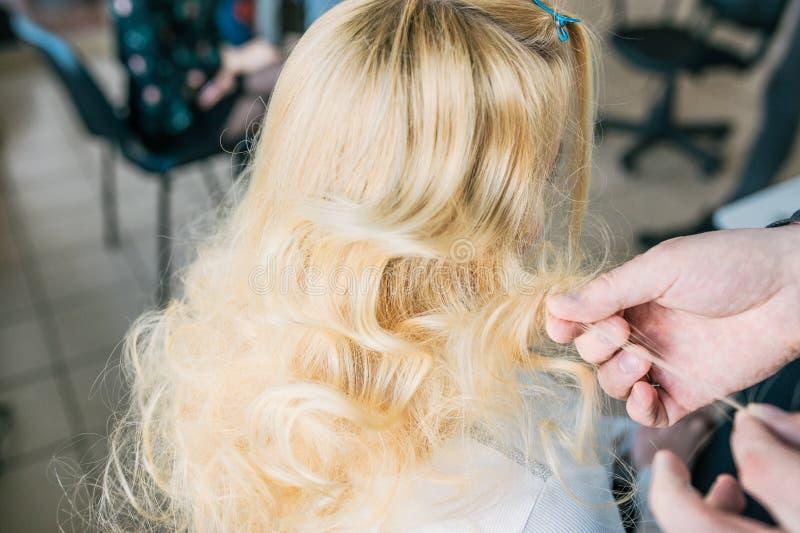 Hintere Ansicht des Friseurs arbeitend mit dem langen blonden Haar ihres Kunden im Friseursalon stockfotos