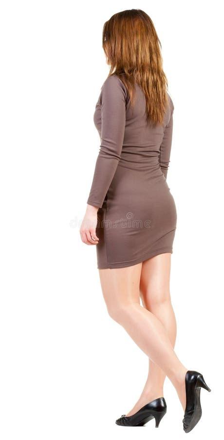 Hintere Ansicht des gehenden Mädchens im braunen Kleid. stockbilder