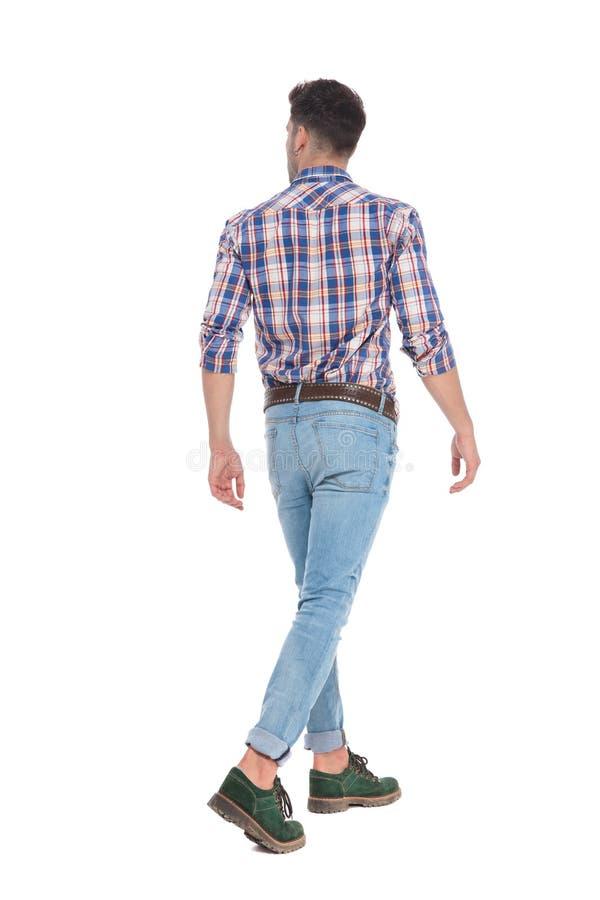Hintere Ansicht des gehenden zufälligen Mannes, der schaut, um mit Seiten zu versehen stockfotos