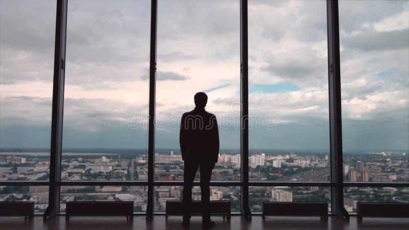 Hintere Ansicht des Geschäftsmannes in einem Büro mit panoramischer Stadtansicht Geschäftsmann bewundert die Stadt von panoramisc stockfoto