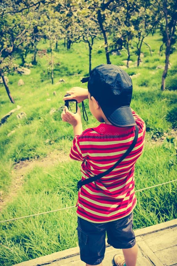 Hintere Ansicht des glücklichen asiatischen Jungen, der sich draußen in der Tageszeit, t entspannt lizenzfreie stockbilder