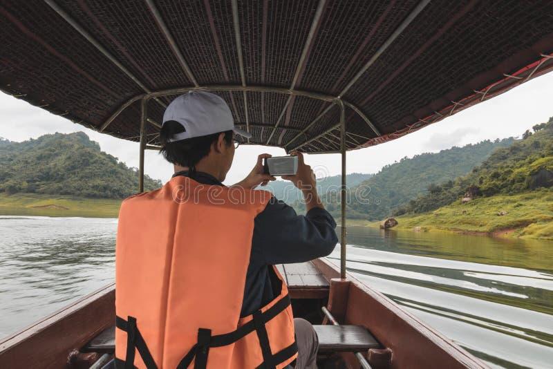Hintere Ansicht des jungen asiatischen Reisendmannes, der auf dem Boot gegen szenischen Gebirgshintergrund sitzt Lebensstil und R lizenzfreie stockfotografie