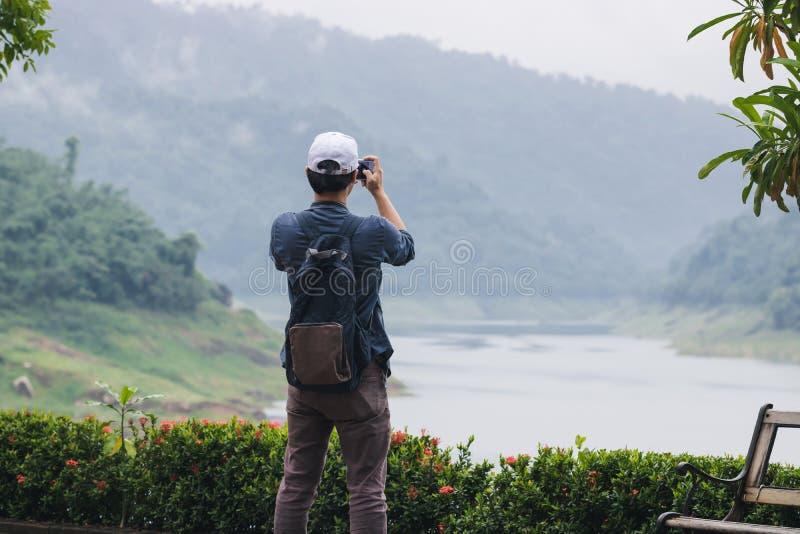 Hintere Ansicht des jungen asiatischen Reisendmannes, der draußen Foto mit beweglichem intelligentem szenischem Hintergrund des T lizenzfreie stockbilder