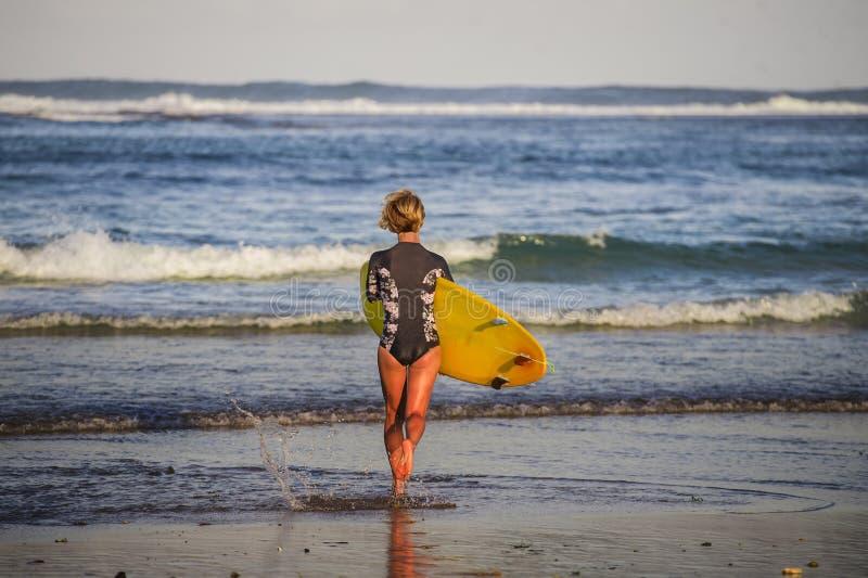 Hintere Ansicht des jungen attraktiven und sportlichen Surfermädchens im kühlen Badeanzug am tragenden Brandungsbrett des Strande lizenzfreies stockfoto