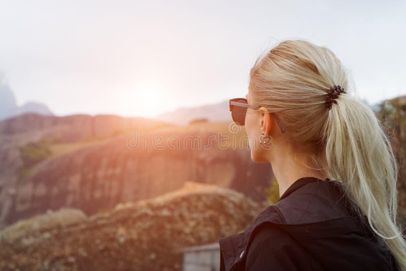 Hintere Ansicht des jungen blonden Mädchens in den Bergen bei Sonnenuntergang stockbilder