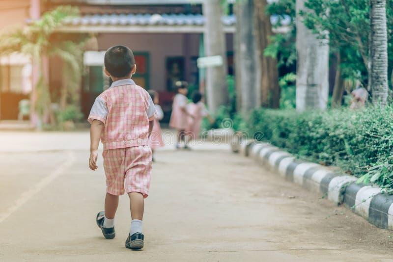 Hintere Ansicht des Jungen folgte Freundinnen auf Stra?e, um zum Klassenzimmer zu gehen lizenzfreie stockfotografie
