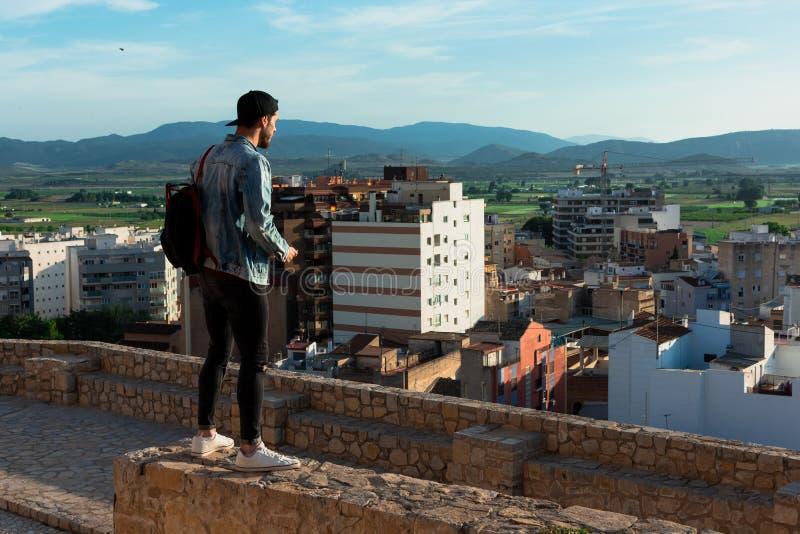 Hintere Ansicht des jungen Mannes Stadt von der Schlossdachspitze betrachtend stockbild