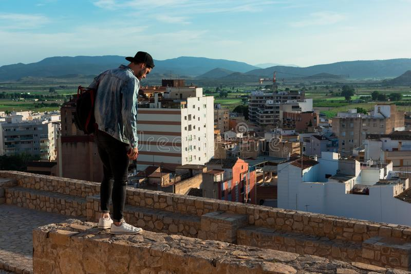 Hintere Ansicht des jungen Mannes Stadt von der Schlossdachspitze betrachtend lizenzfreie stockfotos