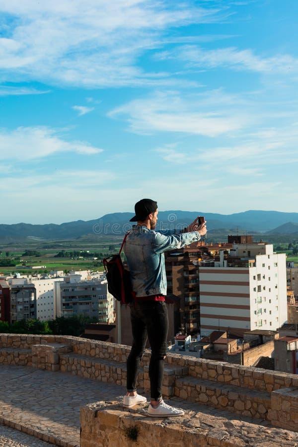 Hintere Ansicht des jungen Mannes Stadt von der Schlossdachspitze betrachtend lizenzfreie stockbilder