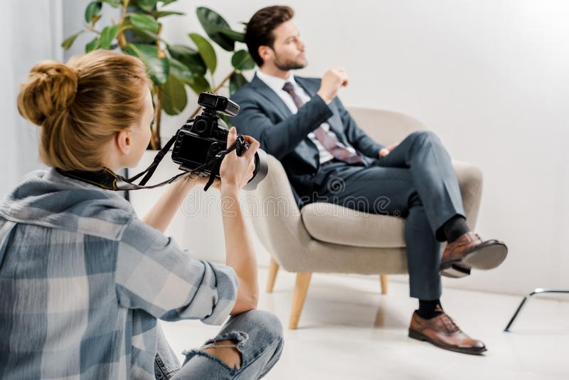hintere Ansicht des jungen weiblichen Fotografen, der hübschen Geschäftsmann fotografiert stockfotos