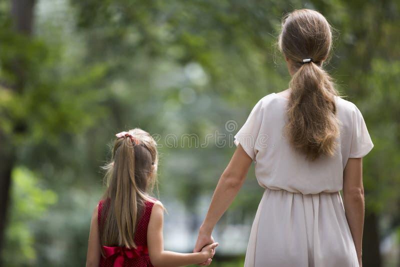 Hintere Ansicht des kleinen blonden langhaarigen Kindermädchens mit der schlanken dünnen Mutter in der modischen Kleidung Händche lizenzfreie stockbilder
