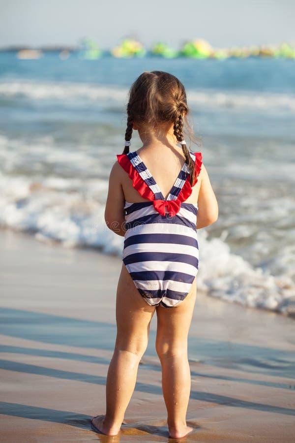 Hintere Ansicht des kleinen Mädchens am Seestrand während der Sommerferien stockfotos