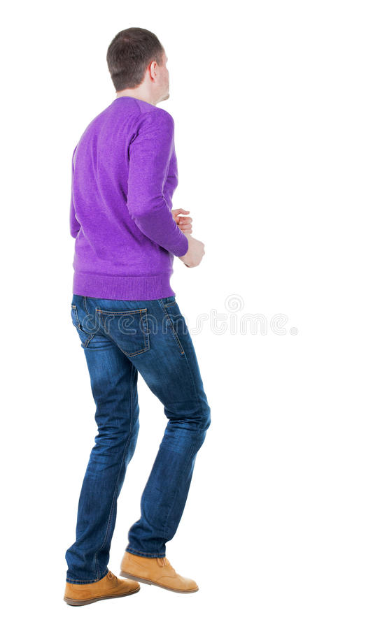 Hintere Ansicht des laufenden Mannes im violetten Pullover stockfotografie
