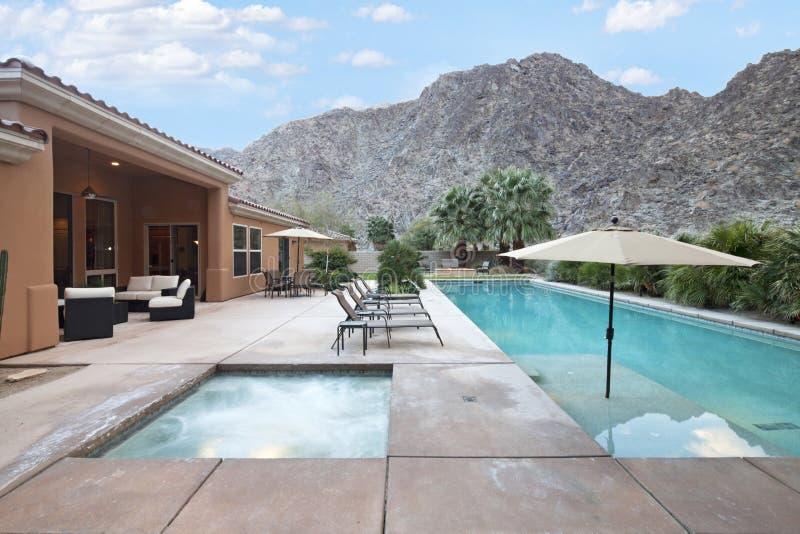 Hintere Ansicht des Luxuslandhauses mit Swimmingpool lizenzfreies stockbild
