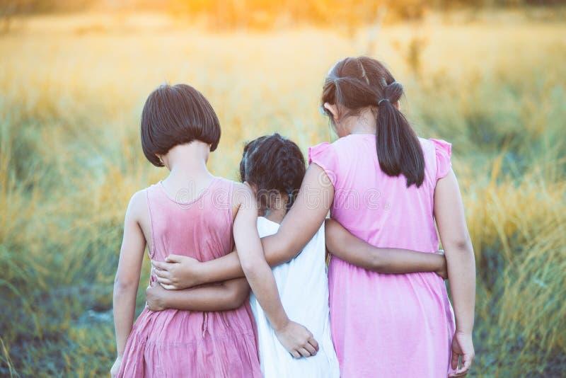 Hintere Ansicht des Mädchens mit drei Asiaten Kinder, dasmiteinander umarmt lizenzfreie stockfotos