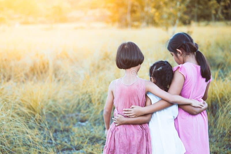 Hintere Ansicht des Mädchens mit drei Asiaten Kinder, dasmiteinander umarmt stockbilder