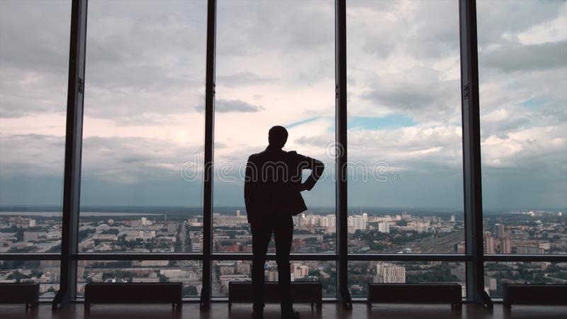 Hintere Ansicht des Mannes in den formalen Reihen, die vor panoramischem Fenster mit Stadtansicht stehen ein Mann steht vor große stockfotografie