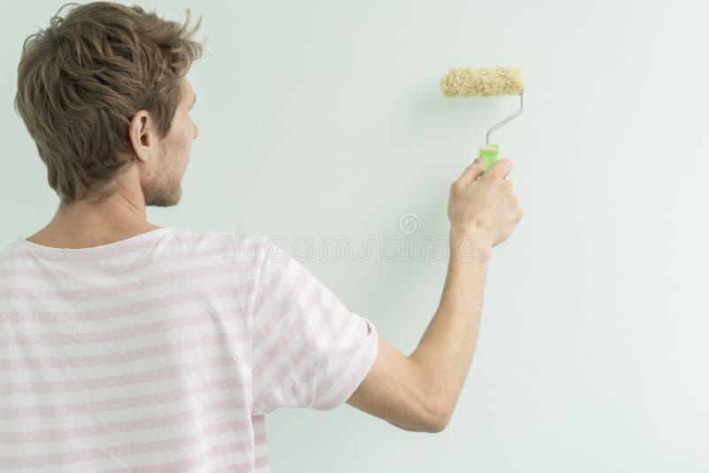 Hintere Ansicht des Mannes die Wand unter Verwendung einer Rollenrosaoberfläche f malend lizenzfreies stockbild