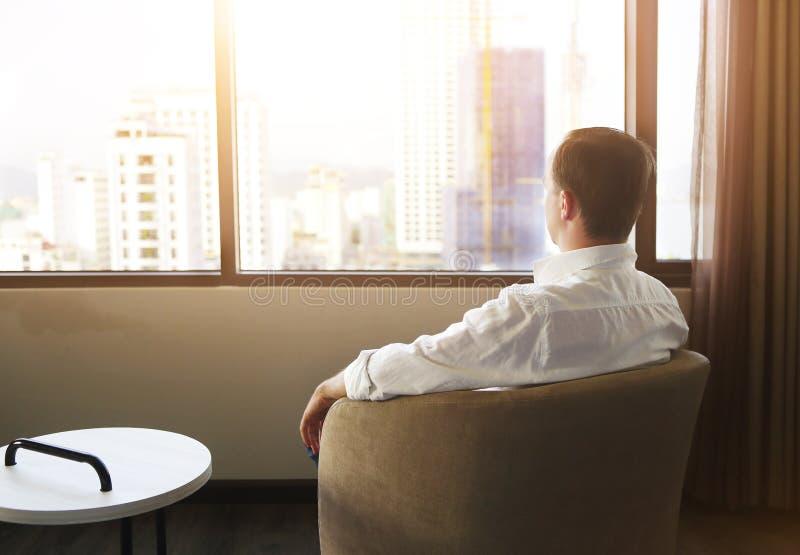 Hintere Ansicht des Mannes entspannend auf Stuhl im Raum stockfoto