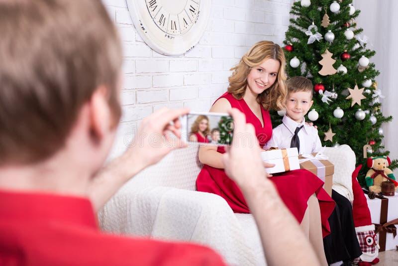 Hintere Ansicht des Mannes Foto seiner Frau und Sohns mit Weihnachten machend lizenzfreies stockbild