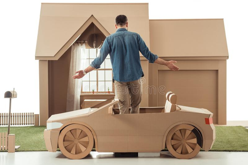 hintere Ansicht des Mannes im Pappauto vor Papphaus stockfotografie