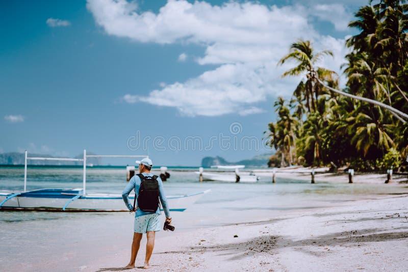 Hintere Ansicht des Mannphotographen mit Kamera auf ursprünglichem Strand Reisender Ausflug die meisten schönen Fotostandortstell lizenzfreie stockfotografie
