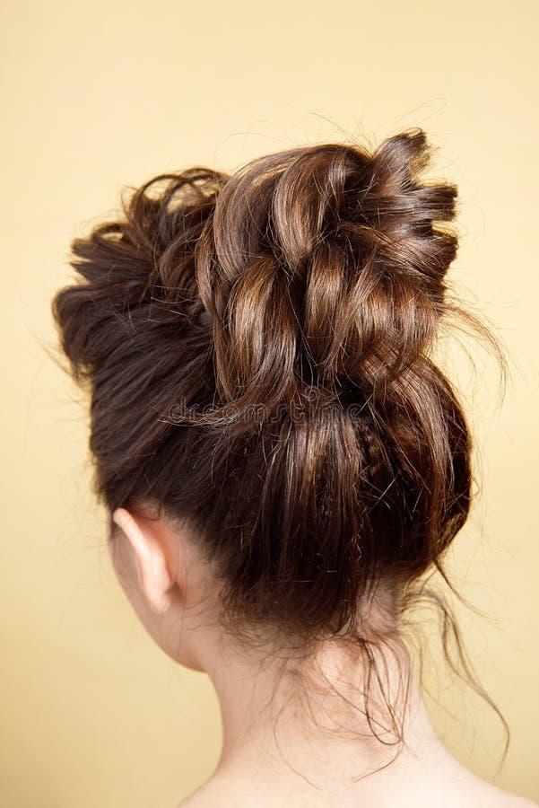 Hintere Ansicht des mittleren Brötchens der weiblichen Frisur auf langem geradem braunem Haar mit radikalem Volumen lizenzfreies stockfoto