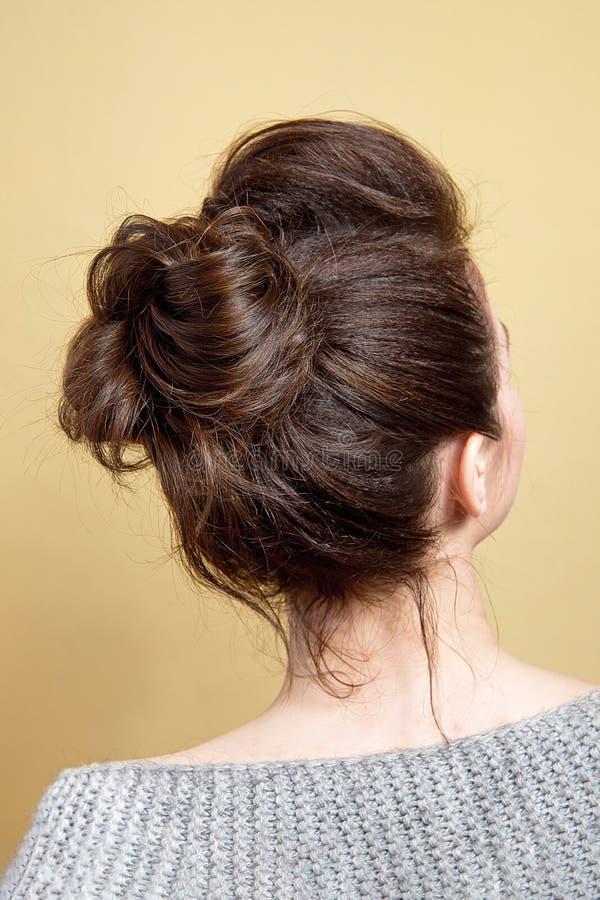 Hintere Ansicht des mittleren Brötchens der weiblichen Frisur auf langem geradem braunem Haar mit radikalem Volumen stockfotografie
