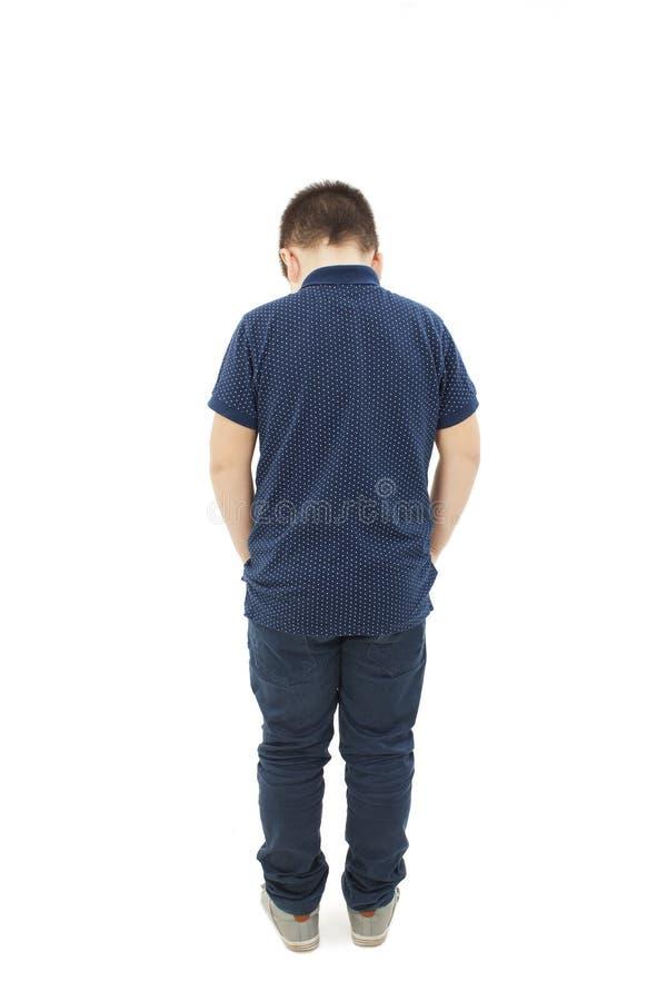 Hintere Ansicht des modernen kleinen Jungen, stehend mit den Händen in den Taschen stockfotos